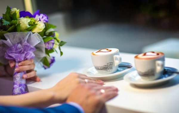 Man and woman's hands with espousal rings, coffee, wedding