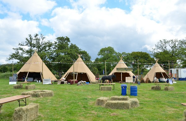 Tipis outside in field