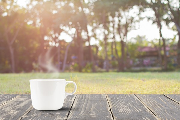 Hot coffee on vintage wooden table top on blurred meadow
