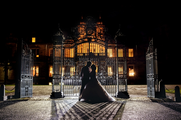 Nighttime wedding couple outside by gate