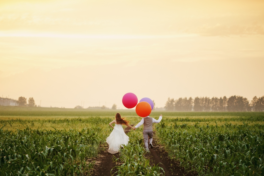 Wedding couple in field with balloons