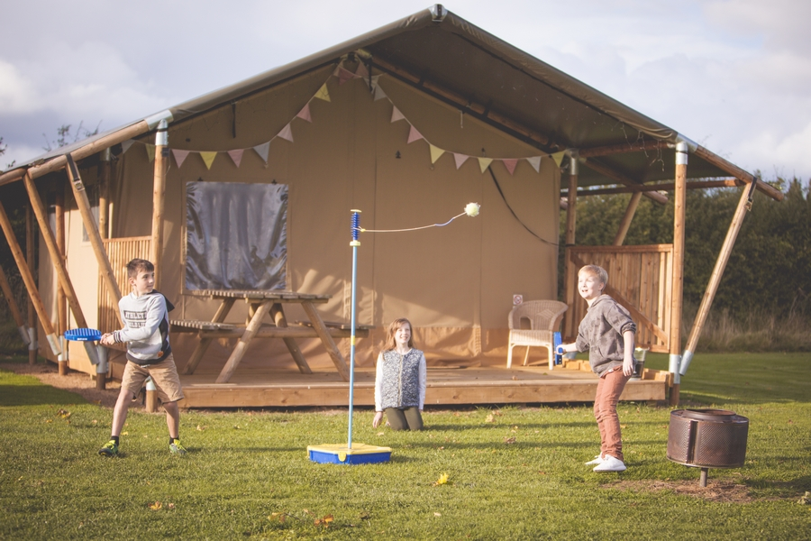 Family playing swing ball at glampsite