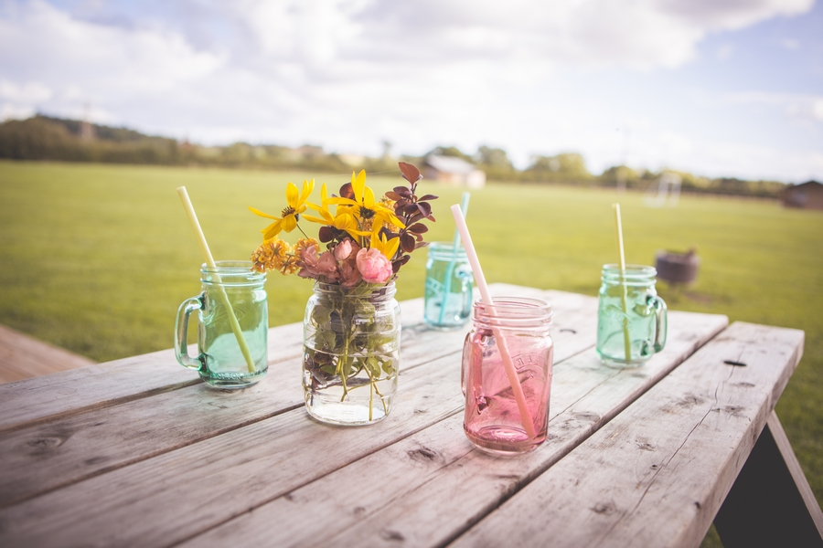 Mason jar glasses and flowers on table outside