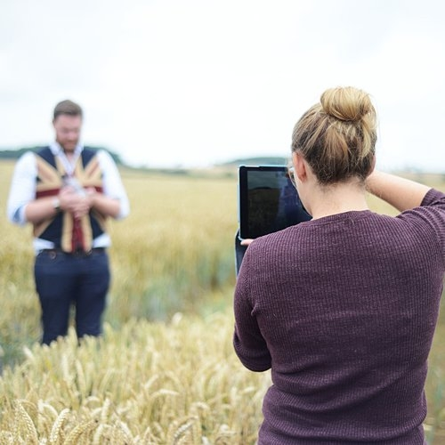 Couple taking photos in field