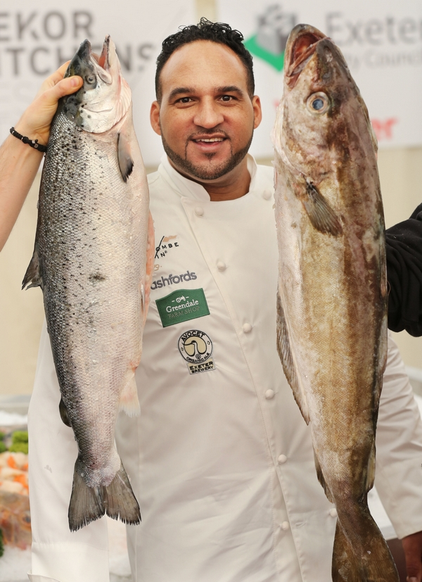 Chef Michael Caines holding two fish at food festival