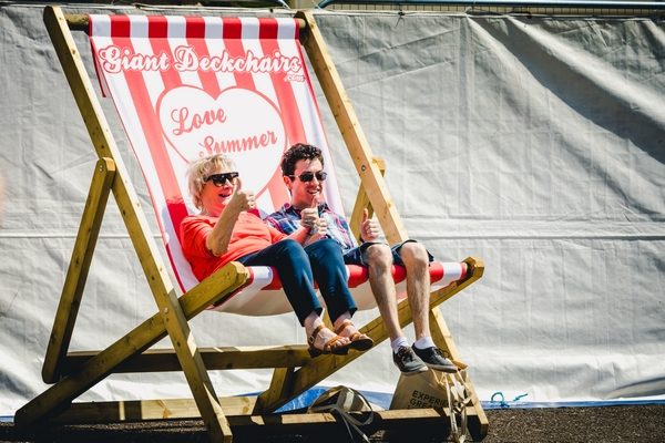 Couple sitting on a giant deckchair at a festival