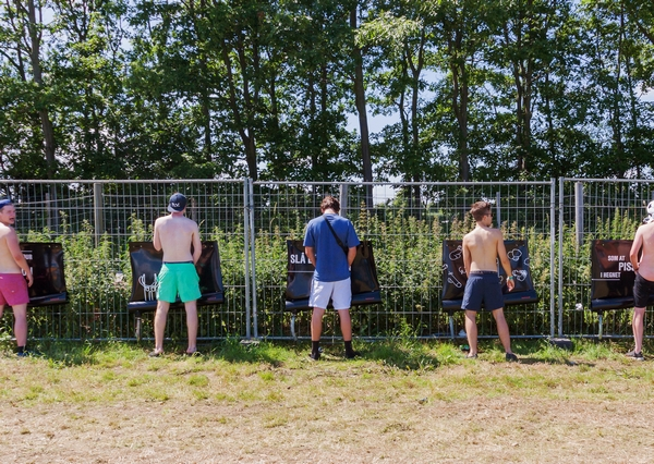 Men using temporary outdoor festival urinals