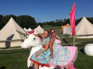 Guests at an outdoor wedding with glamping