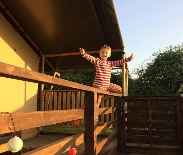 Child climbing fence in sunlight
