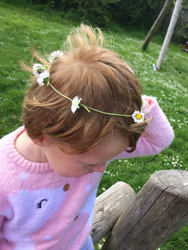 Child with daisy chain on her head