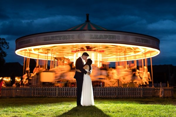 Couple kissing by a carousel