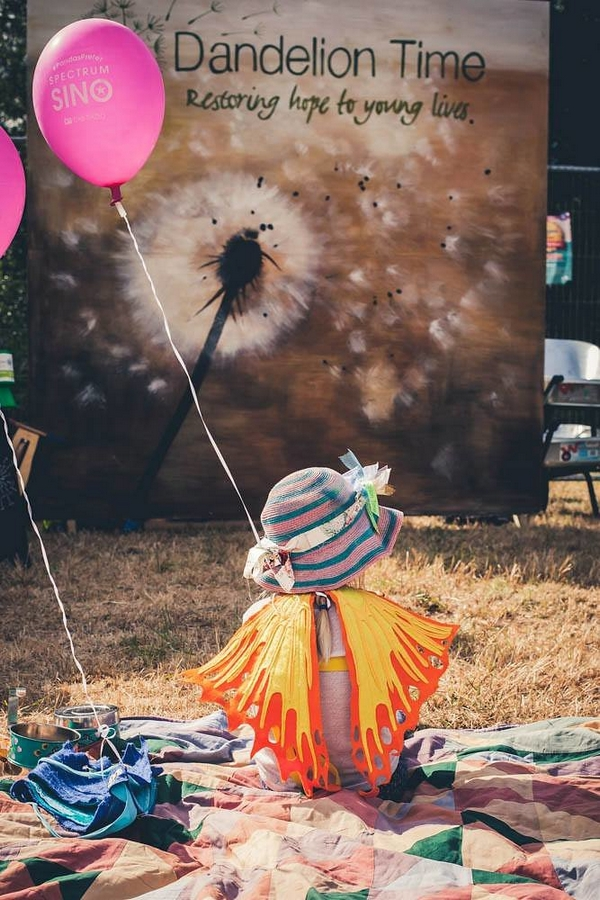 Child holding balloon and wearing fake wings