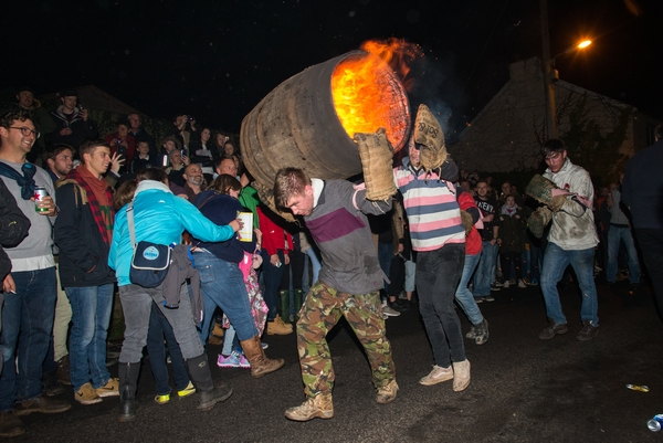 People carrying tar barrel which is on fire