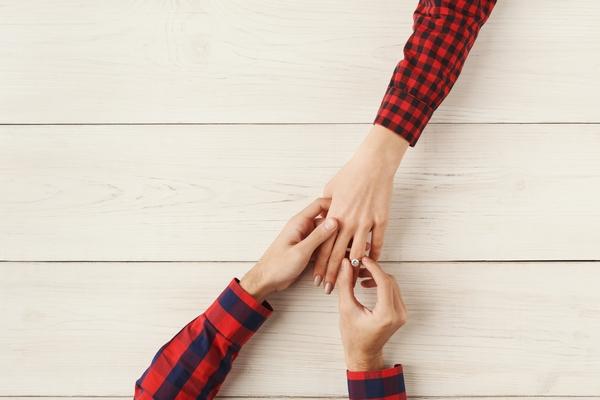 Boyfriend putting ring on girlfriend finger
