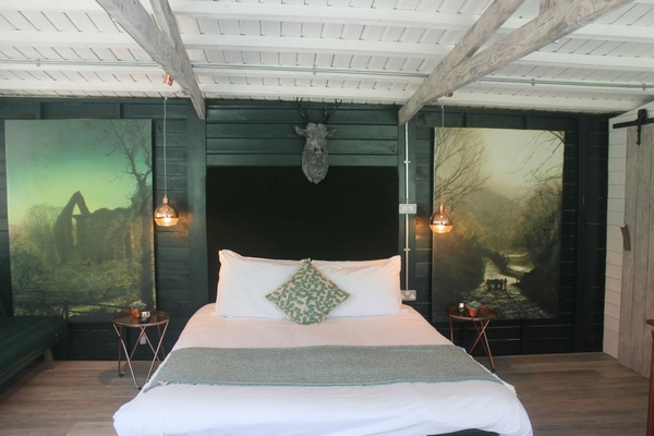 Blue themed room with large landscape paintings