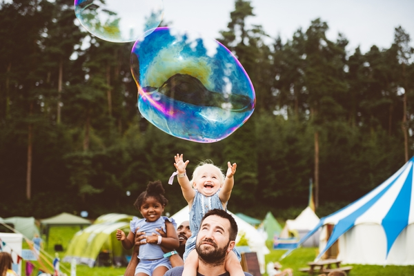 Child sat on Dad's shoulders catching a bubble