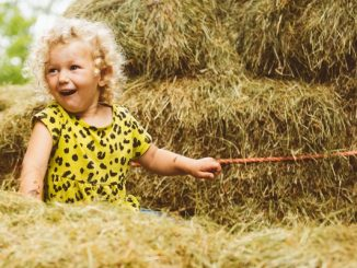 Young child playing on hay bales