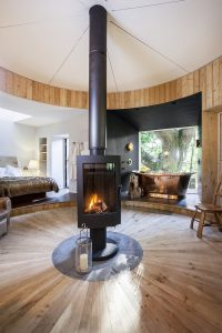 A room with a freestanding woodburner in the centre
