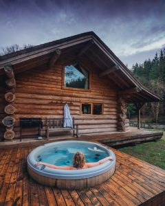 Woman sat in hot tub on deck of wooden hut