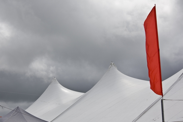 Dark storm clouds approaching an area of white tents