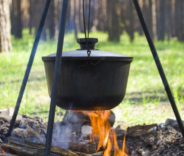 Cooking on a fire at spring. Close view of caldron over the campfire.