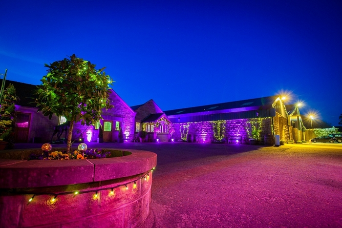 Exterior of Heaton House Farm lit up for guests at night