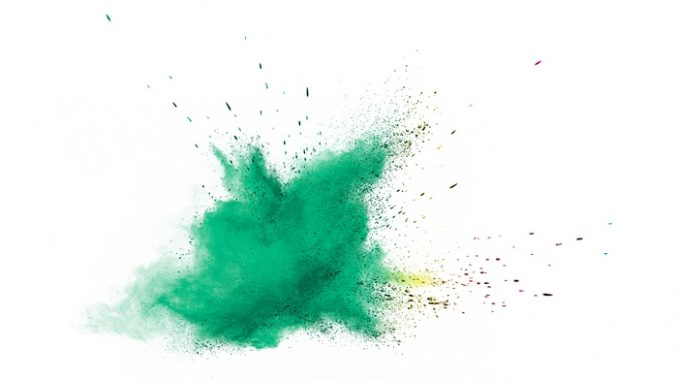 Green powder explosion on white background.
