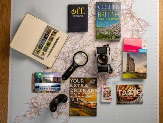 Map laid out with items such as a camera and magnifying glass laid onto