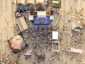 Aerial top view of crowd of people standing near the stage on concert on summer day