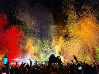 Multi colored confetti above the crowd on music festival.