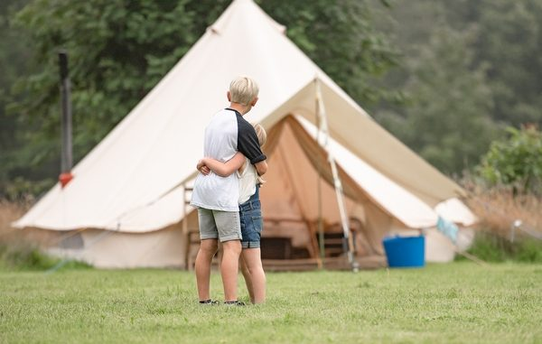 Children hugging in front of a tent