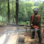 Ben Carden chopping a tree in the woods