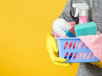 Person holding basket of cleaning utensils