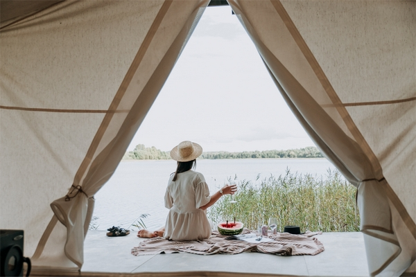 Lady sat having a picnic whilst glamping