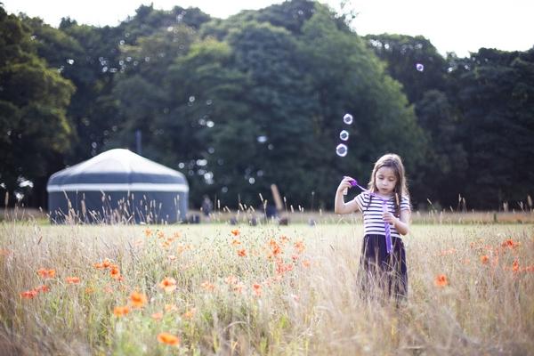 Girl blowing bubbles in a field