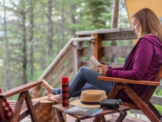 Lady sat on a deck reading